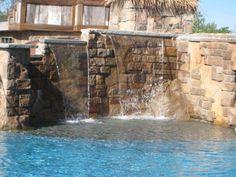 Custom water fall with a beautiful stone wall, and sun ledge below!