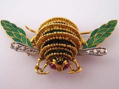 An 18 carat gold insect brooch set with diamonds and rubies and decorated with green enamel #jewellery
