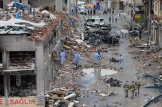 AFTERMATH: Forensic experts worked as soldiers patrolled Sunday in Reyhanli, Turkey, near Syria, where two car bombings killed at least 46 people a day earlier. Authorities blame groups connected to Syria's intelligence service and said that nine Turkish citizens had been arrested. (Associated Press)