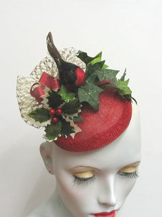 Christmas , and what better time than to glam up, go the whole hog, be festive and wear a red robin and holly berry hat :) This fascinator has been made with a 5 inch red sinamay base covered in faux ivy, berries, a red feather robin and metallic gold veiling The fascinator has a millinery elastic to the underside, which means it can be worn either side of the head. Handmade in England by me with love and care