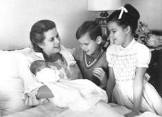 Princess Grace holding her four-day-old daughter, princess Stephanie while her children are looking at their new sister.