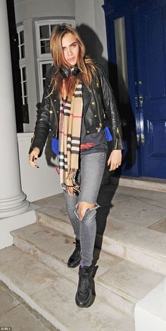 Cara Delevingne wraps up warm with a Burberry scarf while leaving her west London home