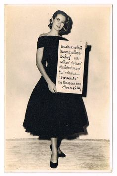 Grace Kelly holding a Thai poster advertising The Vagabond King, a 1956 musical film adaptation of the 1925 operetta by Rudolf Friml.
