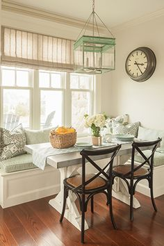 A free-standing, zinc-topped table cozies up to an L-shaped window seat in this eat-in kitchen by JS Interiors, Boston.