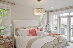 Beautiful bedroom centered around neutral tones of white, cream and taupe with pops of gold and coral | Blanco Interiores