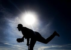 Toronto Blue Jays pitcher Ramon Ortiz is silhouetted while warming up during baseball spring training in Dunedin, Fla., on Friday, Feb. 22, 2013. (AP Photo/The Canadian Press, Nathan Denette)