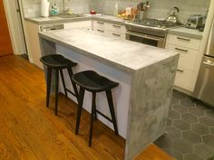 """Cast in place concrete countertops. 1.5"""" - thick with waterfall walls on the island and an overhang for stools."""