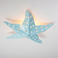 """Hand cut tin forms this unique starfish ceiling light. Ours exclusively, it comes in the basic burnished tin (Bronze), Coral, Metallic Gold, White, Yellow, or the sea like colors of Spa Blue, Turquoise and Navy. 2x60 watts. Double socket. (6""""Hx24""""W) Ceiling Cap: 5"""" round. Torpedo bulbs recommended."""