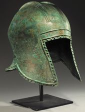 Left side, slanted right; Type II Helmet.  Materials; metal alloy. Culture; Illyrian Technique; This helmet is formed from a piece of sheet metal. Formed in a mould with the finer details repoussé (embossed). The purpose of the design is to protect the face and neck and allow blows to glance off.  SOLD COPYRIGHT © Royal Athena