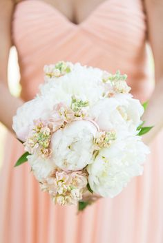The bridesmaid bouquets feature white peonies and peach stock to match their Laura style Donna Morgan dresses.