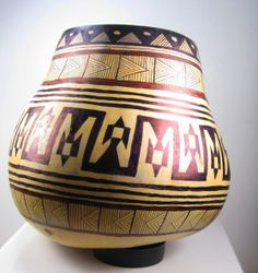 SOLD - Small canteen gourd painted black, then hand-carved with tribal inspired designs, figures and symbols. Sealed with wax coating. Round leather cord added as hanger for decorative vase. View...
