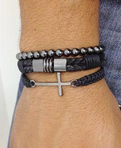 Kit de pulseiras unissex composto de 3 pulseiras, sendo:  - 1 pulseira shambala confeccionada em macramê com cordão encerado na cor preto e crucifixo em banho grafite.  - 1 pulseira de couro trançado na cor preto e entremeios metálicos em banho grafite  - 1 pulseira de pedra natural hematita de 6...