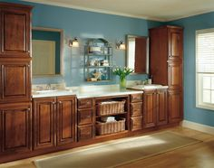 This ocean-inspired master #bathroom makes the most of its available space with two sinks and beautiful Diamond #Cabinets. The Selena cabinet door style in gorgeous Cherry Coffee finish is the perfect contrast to the light-colored hardwood floors, blue walls and white countertops.  All combine to complete the look of this seaside retreat.