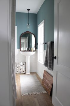 Our favorite part of this modern farmhouse bathroom remodel was the white subway tile paired perfectly with grey grout all around the room. The antique mirror and modern pedestal sink finished off the space perfectly overtop of medium wood look tile. Pedastal Sink, Modern Pedestal Sink, Pedestal Sink Bathroom, Bathroom Renos, Master Bathroom, Bathrooms, White Subway Tile Bathroom, Country Interior Design, Grey Grout
