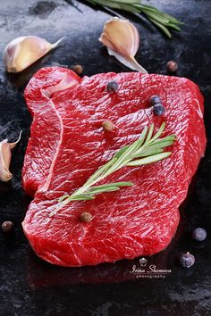 Cut of raw beef with spices on a black background