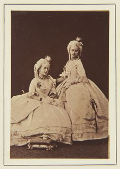 Photograph of a full length portrait of Princess Helena (1846-1923), later Princess Christian of Schleswig Holstein, seated on the left and Princess Louise (1848-1939), later Duchess of Argyll, standing on the right. Both Princesses wear the dresses they wore at a Fancy Ball at Claremont in Feb.1865.