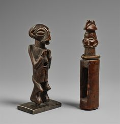 A YAKA SLIT DRUM AND A SMALL YAKA FIGURE Democratic Republic of the Congo The drum with head finial with tall median crest, brass ring around the neck; the figure with hands of chest and fetish cavity in the abdomen, dark patinas. 12 cm. and 13.5 cm. high