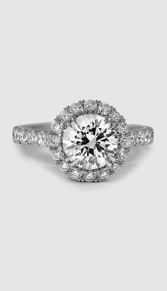 Elegant French pavé set diamonds form a stunning halo around the center gem in this beautiful engagement ring.