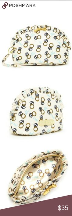 """Betsy Johnson Cosmetic Bag A charming ring print decorates the inside of a zip top cosmetic bag trimmed with ruffles.  - Single wrist strap with wedding ring charm - Zip top closure - Exterior features ruffle trim, glitter bow, and glitter text print or allover print - Approx. 5.5"""" H x 8.5"""" W x 3.25"""" D - Approx. 5.5"""" strap drop Betsey Johnson Bags Cosmetic Bags & Cases"""