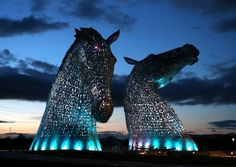 The Kelpies statues lit up at Helix Parkland in Falkirk, Scotland.  Built of structural steel with a stainless steel cladding, the Kelpies are 30 meters high (98.425 feet) and weigh in at 300 tons. The Kelpies were designed by artist Andy Scott and are a monument to horse powered heritage across Scotland, giving the area proud equine guardians.