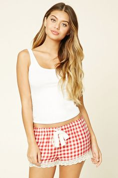 A pair of woven plaid PJ shorts featuring a scalloped lace trim at the hem and an elasticized drawstring waist.