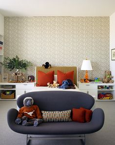 Modern blue sofa, patterned wallpaper, red accent pillows, orange lamp, white bedside storage tables.