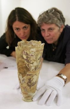 (L-R) Exhibition co-ordinator Helene Vassal and restorer Beatrice Beillard examine a painted glass gobelet from the 1st or 2nd century, as they unpack items in preparation for the 'Afghanistan, Rediscovered Treasures' exhibition at Mus?e Guimet on October 9, 2006 in Paris, France. The national museum in Kabul, which is currently being completely rebuilt after twenty years of war, is exhibiting its treasures at the Guimet museum in Paris. The museum is helping to restore a part of ...