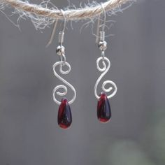 I handmade these earrings of deep red Czech glass and silver plated wire. They are twisted to resemble a small swirl or a whirlpool.