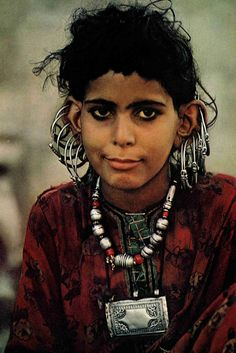 "Oman | ""Silver rings dangle from her ears, a country girl dons family wealth for a visit to Matrah, Oman's largest city.  The tooled case contains Koran verses for good luck.  At puberty, wealthy girls begin wearing veils before strangers"" 