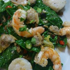 A medley of shellfish (King prawns, scallops & clams) on a bed of sprout tops sauteed with chilli & garlic
