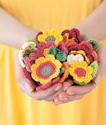 Crocheted flowers. I'm thinking I'll make one to add to a baby sweater I'm knitting. For a gift. Now, someone, have a baby girl!