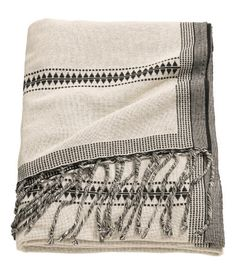 Natural white/striped. Jacquard-weave throw in a soft cotton blend with fringe at short sides. Pattern inverted at back.