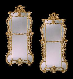 A fine and important pair of mid 18th century carved giltwood border glass mirrors in the manner of William and John Linnell, having 18th century replacement plates divided by a rocaille carved fillet, with straight cresting surmounted by stylised pierced foliate plumes, and serpentine sides with pierced C-scrolls with cascading floral garlands; having shaped apron centred by a foliate cartouche.