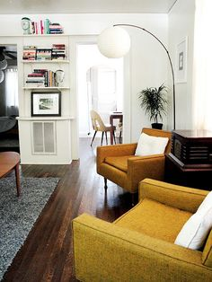 living room. - love the mustard chairs, dark floors and crisp white walls, all with the touch of chrome