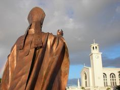 Dulce Nombre de Maria {Sweet Name of Mary} Cathedral Basilica and a statue of Pope John Paul II in Hagatna, Guam.