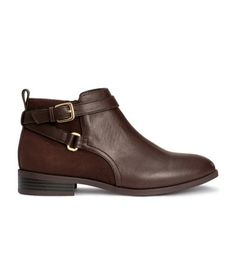 Jodhpur boots in imitation leather with back section in imitation suede, decorative ankle straps with metal buckles, and side zip. Rubber soles. Heel height 1 1/4 in.