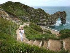 DORSET, UNITED KINGDOM - JULY 13: In this handout image provided by LOCOG, Torchbearer 045 Lisa Devine holds the Olympic Flame in front of Durdle Door on the Jurassic coast, during Day 56 of the London 2012 Olympic Torch Relay on July 13, 2012 in Dorset , England. The Olympic Flame was on day 56 of a 70-day relay involving 8,000 torchbearers covering 8,000 miles.
