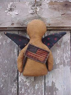 """Primitive Americana Angel Ornie Extreme primitive angel made of stained muslin with stained fabric wings. Attached is a stained fabric flag, with twig pole, hand stitched to stained felt. Comes with a rusty wire hanger. Approximately 6"""" tall with a wing span of 6 3/4"""". An original LAZARUS creation http://www.lemonpoppyseeds.com/shoppes/pslazarusprimitivefolkart/"""