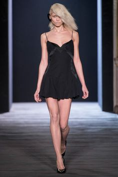 FALL 2013 RTW  Hakaan /   The task for Yildirim was to give himself a jump-start. Souped-up party clothes are as likely to do the trick as anything, They're also solidly in the Hakaan repertoire. Working in only black, white, and red, he showed long column gowns with a gothic sensibility, tiny slipdresses that combined matte and shine, and elaborately constructed, peplumed bustier tops worn with sheer trousers or a see-through pencil skirt.