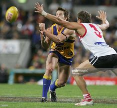 Ben Cousins #9 of the Eagles gets his handball away ahead of Byron Schammer #3 of the Dockers during the round 20 AFL match between the West Coast Eagles and the Fremantle Dockers at Subiaco Oval on August 12, 2005 in Perth, Australia.