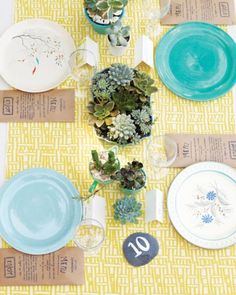 The table decor includes paper-envelope menus, painted-rock numbers, vintage china, and centerpieces of succulents.