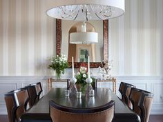 A long, wooden table is centered under an elegant chandelier in this traditional dining room. Neutral striped wallpaper and wainscoting bring classic style to the space.