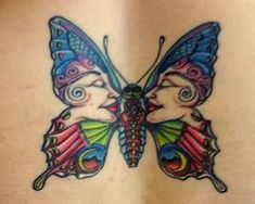 A hippy butterfly tattoo that has womens faces in the patterns on the wings