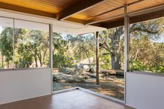 Situated on the eastern end of the residence, the master bedroom boasts a mitered glass corner window that overlooks a koi pond and a Live Oak tree.