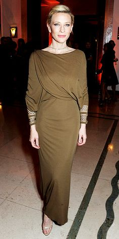 CATE BLANCHETT The star is all kinds of stylish in a draped olive-green creation with a sexy rear view (open back, high center slit) featuring mesh insets the wrists, plus a tassel necklace worn backward, for the Women of the Year event in London.