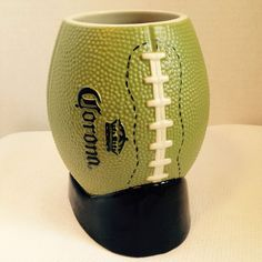 New Corona Beer Mug or Cup made out of Ceramic with a light glaze. This mug features a green football with a textured finish to look just like a real football. The black stand is part of the mug.