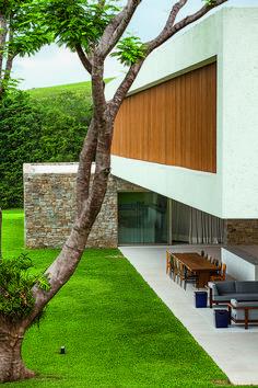 O desejo de unir pais, filhos e netos deu origem a uma casa emoldurada no verde, representado por árvores delgadas, um lago generoso e um paisagismo inspirador.