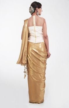 Carry Corset Gold Shimmer  by Preeti Singhal This is a golden and white lama shimmer saree with corset. It features stone embellishments and sequin work on the corset. It has embellished tassels attached to the palla