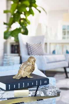 Coffee table books topped with decorative gold bird.