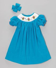 Boasting an easy-breezy construction and buttoned back, this fetching frock slips on the sweetness in seconds. Detailed smocking lends a touch of festive fun, while a plush, coordinating bow finishes the look like a cherry on top.